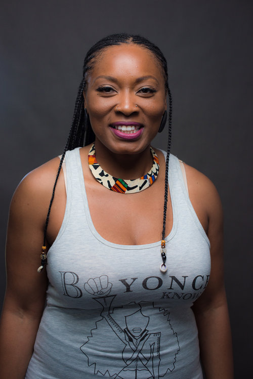 "EbonyJanice is smiling wearing a tank top of her own design that reads, ""Beyonce Knows"" with an image of Beyonce with her fist in the air, replacing the E with her fist. She's wearing a printed necklace and braids in her hair with beads and shells at the end."