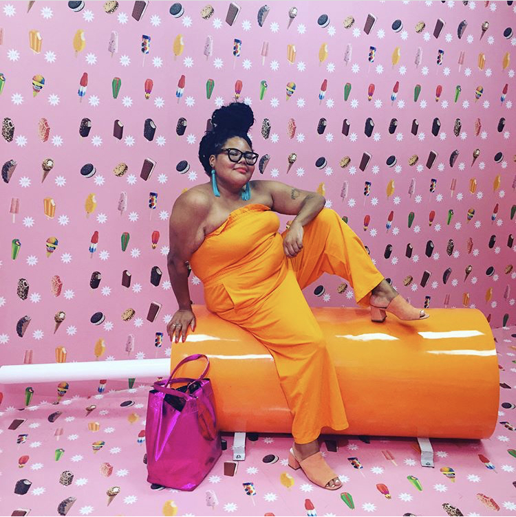 Candace sits in an ice cream museum atop a creamsicle seat, wearing an orange jumpsuit, peach mules, and a metallic pink tote. Her hair is in a bun atop her head and she's smiling, wearing bright blue earrings.
