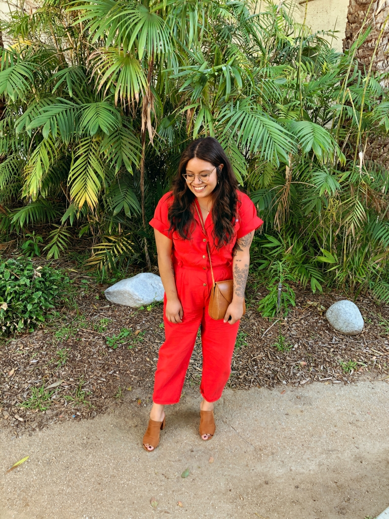 Sally is a 5'1, mid size, brown Latina woman with mid length hair. She wears a bright red jumpsuit, caramel color cross shoulder purse and high heel peep toe clogs. She smiles and looks down against a backdrop of green bamboo and palm leaves.